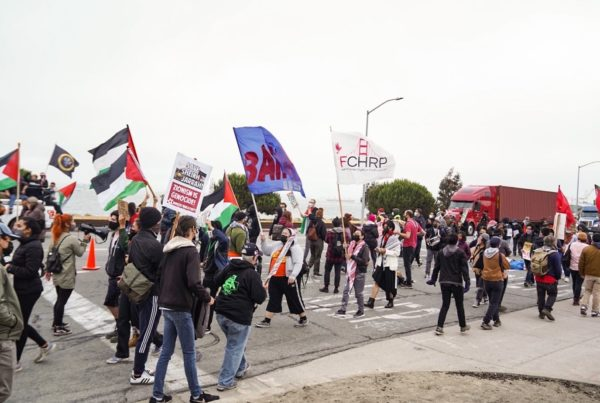 """A crowd of people holding Palestinian flags, signs reading """"Save Sheikh Jarrah"""" and """"Zionism is genocide!"""" during Block the ZIM Boat event on June 4, 2021."""